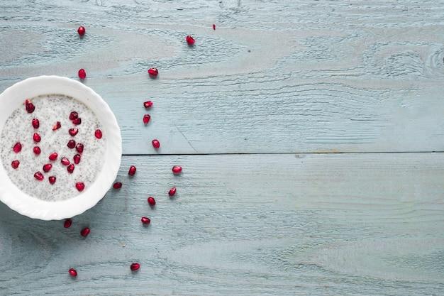 Una vista elevata del budino del seme di chia in ciotola bianca sulla tavola di legno