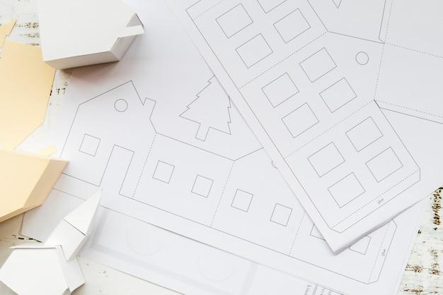 Una vista elevata del modello di casa di carta creativa e carta bianca sul tavolo