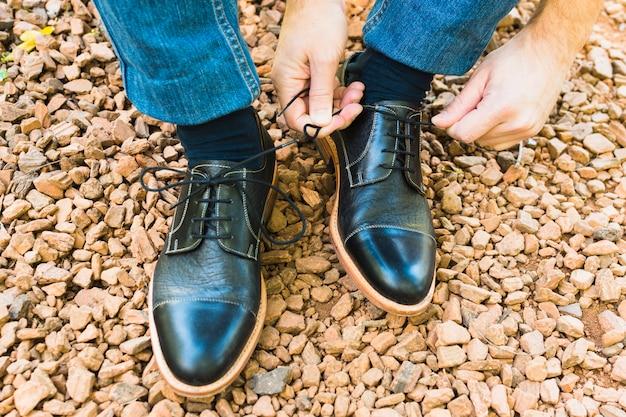 Una vista elevata del piede dell'uomo sul ciottolo che lega i lacci delle scarpe