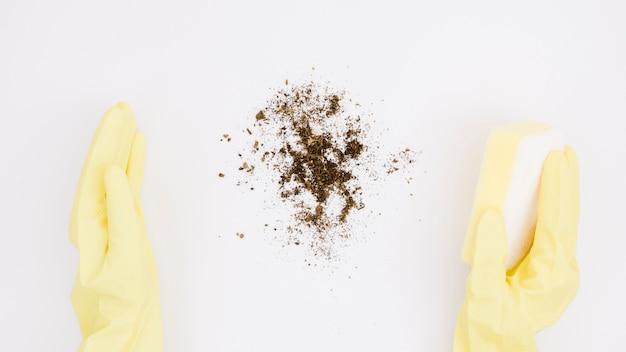 Una vista elevata della mano che indossa guanti per pulire la polvere con spugna su sfondo bianco