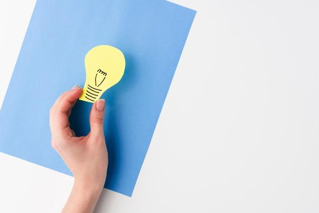 Una vista elevata della mano femminile che tiene il ritaglio della carta della lampadina sopra la carta blu della carta