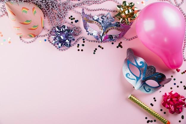 Una vista elevata della maschera di carnevale di travestimento due con il materiale della decorazione del partito sopra fondo rosa