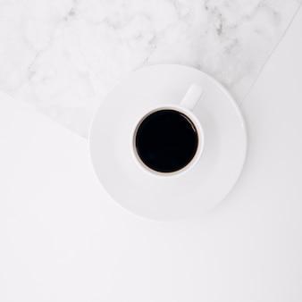 Una vista elevata della tazza di caffè nero sul piattino sullo sfondo di marmo e bianco