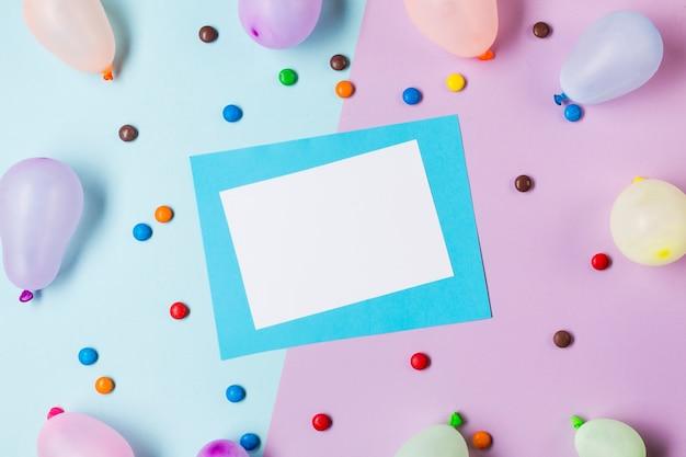 Una vista elevata di carta bianca e blu circondata da gemme e palloncini su sfondo blu e rosa
