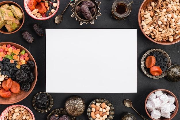 Una vista elevata di carta bianca vuota circondata da deliziosi frutti secchi; noci e dolci per il ramadan su sfondo nero con texture