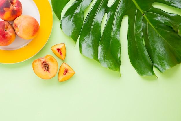 Una vista elevata di frutta pesca con foglia verde monstera su sfondo pastello