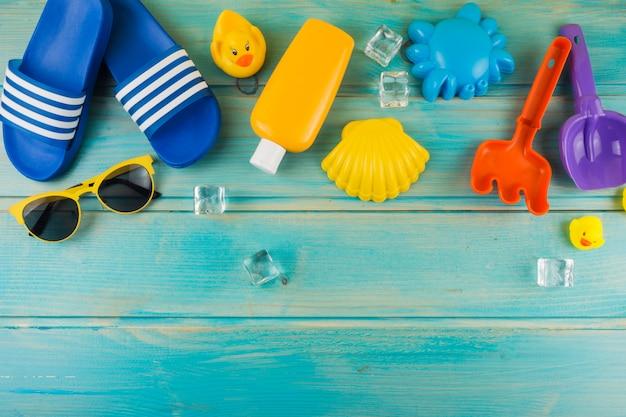 Una vista elevata di occhiali da sole; cubetti di ghiaccio; ciabatte infradito; papera di gomma; giocattoli sulla scrivania in legno turchese