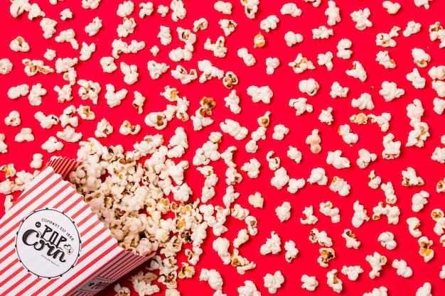 Una vista elevata di popcorn versati salati dalla scatola su sfondo rosso