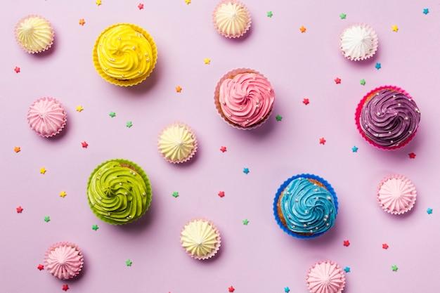 Una vista elevata di stelle colorate spruzza; aalaw e muffin su sfondo rosa