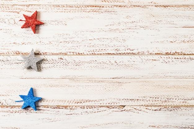 Una vista elevata di stelle glitter su sfondo bianco superficie di legno