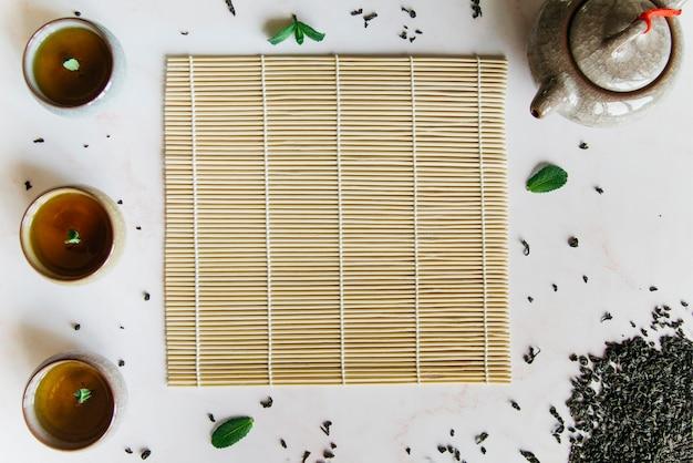 Una vista elevata di tazze da tè alle erbe con tovaglietta; teiera e foglie secche su sfondo bianco
