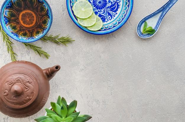 Una vista elevata di tè al limone e zenzero con ingredienti su sfondo concreto