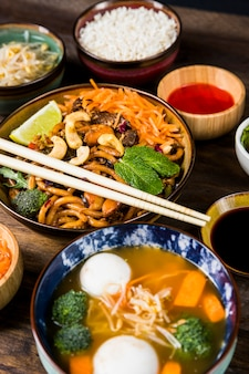 Una vista elevata di thai udon noodles e zuppa con polpette di pesce e verdure