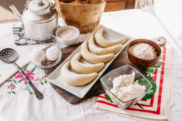Una vista frontale bagel all'interno del piatto bianco buonissimo insieme a farina e uova sul tavolo prodotti biscotto