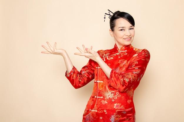 Una vista frontale bella geisha giapponese nel tradizionale abito rosso giapponese con bastoncini di capelli in posa con le mani in piedi sorridente sullo sfondo crema cerimonia divertente giappone est