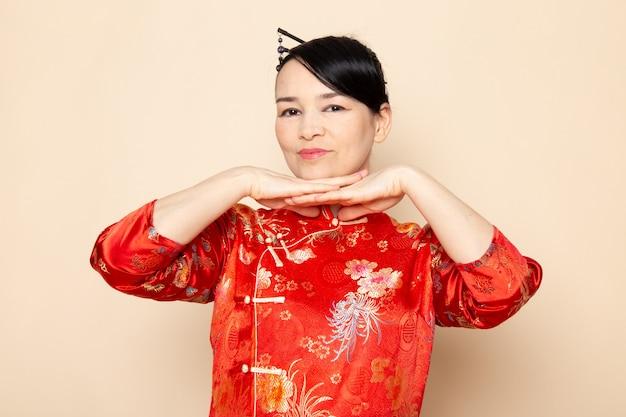 Una vista frontale bella geisha giapponese nel tradizionale abito rosso giapponese con bastoncini di capelli in posa con le mani in piedi sullo sfondo crema cerimonia divertente giappone orientale