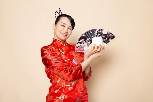 Una vista frontale bella geisha giapponese nel tradizionale abito rosso giapponese con bastoncini per capelli in posa tenendo ventaglio pieghevole e candela bianca elegante sullo sfondo crema cerimonia giappone