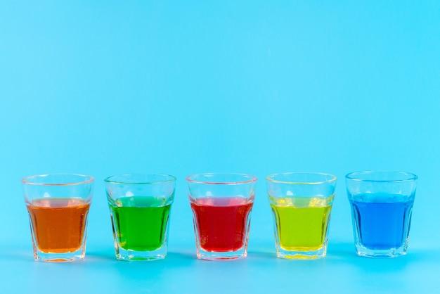 Una vista frontale bevande colorate all'interno di bicchieri che si raffreddano su ghiaccio color blu, succo di frutta