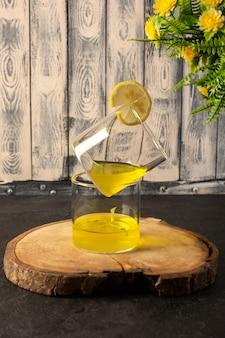 Una vista frontale bicchieri con succo di succo di limone all'interno di bicchieri trasparenti insieme a fiori sulla scrivania in legno marrone e sfondo grigio cocktail bevanda al limone
