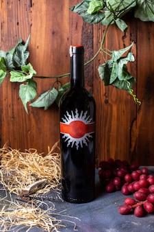 Una vista frontale bottiglia di vino rosso di vino rosso insieme a bacche rosse e foglie verdi isolati sulla bevanda grigia cantina cantina alcol