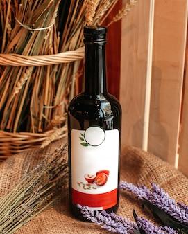 Una vista frontale bottiglia di vino rosso nero insieme a fiori viola sulla superficie di legno marrone