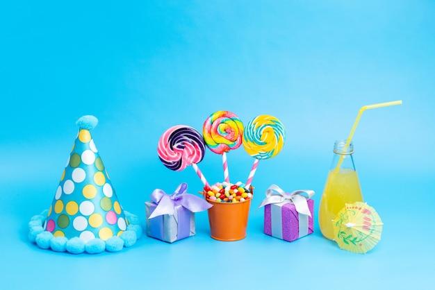 Una vista frontale caramelle colorate con lecca lecca arcobaleno e piccole confezioni regalo cocktail sul blu