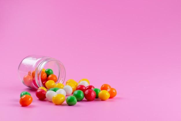 Una vista frontale caramelle colorate dolci e appiccicose sul colore rosa, confetteria a base di zucchero di colore