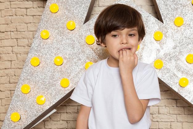 Una vista frontale carino ragazzino in maglietta bianca jeans scuri sulla stella progettato supporto giallo e sfondo chiaro
