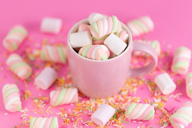 Una vista frontale che mastica marshmallow all'interno di rosa, tazza e tutto in rosa, confettura di zucchero arcobaleno di colore