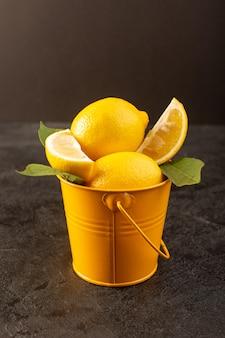 Una vista frontale chiusa limoni freschi gialli morbidi e succosi interi e affettati all'interno del cestino giallo sparsi con foglie verdi sul buio