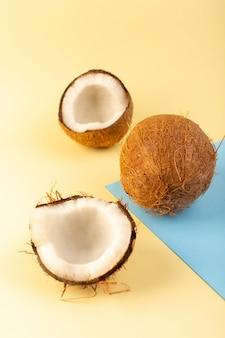 Una vista frontale chiusa noci di cocco intere e affettate latteo fresco dolce isolato su sfondo color crema-ghiacciato-blu tropicale frutta esotica dado