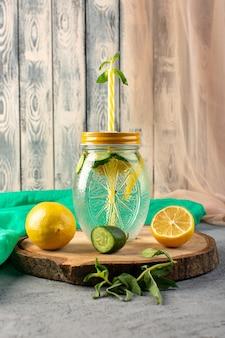 Una vista frontale cocktail di limone bevanda fresca fresca all'interno della tazza di vetro fette limoni cetrioli paglia sulla scrivania in legno e sfondo grigio cocktail drink frutta