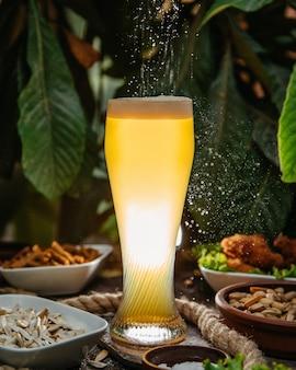 Una vista frontale cocktail ghiacciato in bicchiere lungo con piatti e noci sul tavolo bere succo di ghiaccio cocktail