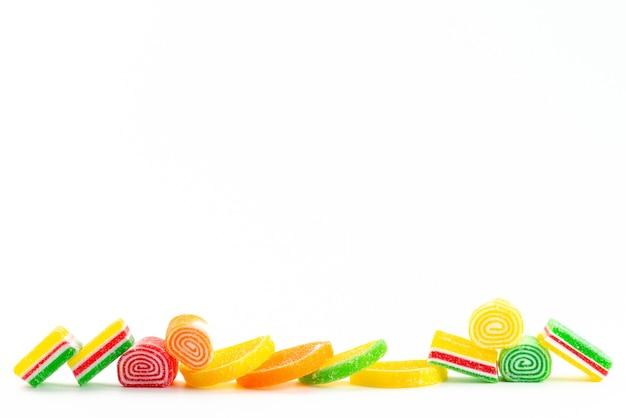 Una vista frontale confettura colorata appiccicosa e dolce isolata sul colore bianco, dolce della pasticceria di zucchero