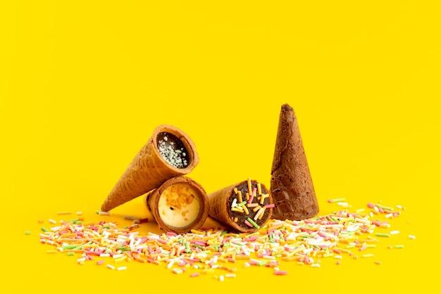 Una vista frontale corna gelato insieme a particelle di caramelle multicolori su giallo, colore zucchero candito dolce