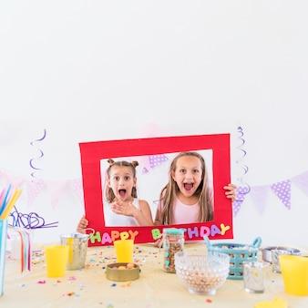 Una vista frontale di due ragazze che tengono la cornice del testo di compleanno dietro il tavolo alla festa