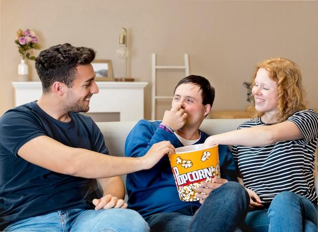 Una vista frontale di tre amici che mangiano popcorn a casa