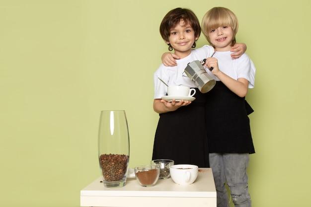 Una vista frontale due ragazzi felici in magliette bianche che preparano il caffè beve sullo spazio colorato di pietra
