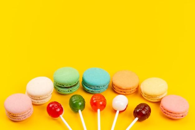 Una vista frontale francese macarons con lecca-lecca su giallo, torta di zucchero candito