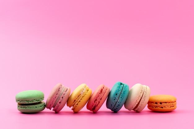 Una vista frontale francese macarons rotondo delizioso colorato isolato su rosa, pasticceria biscotto torta