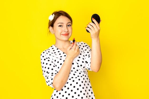 Una vista frontale giovane bella femmina in abito bianco e nero a pois facendo il trucco su sfondo giallo abbigliamento moda mascara rossetto pennello