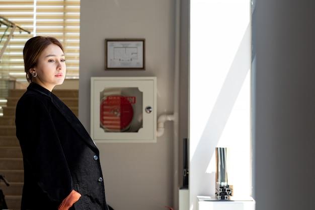 Una vista frontale giovane bella signora in camicia bianca pantaloni neri giacca scura guardando la distanza nella hall in attesa durante le attività di lavoro di costruzione durante il giorno