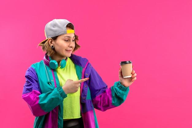 Una vista frontale giovane bella signora in camicia color acido pantaloni neri giacca colorata con auricolari blu tenendo skateboard