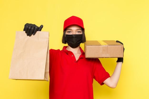 Una vista frontale giovane corriere femminile in uniforme nera guanti neri maschera nera e berretto rosso in possesso di scatola e pacchetto di cibo