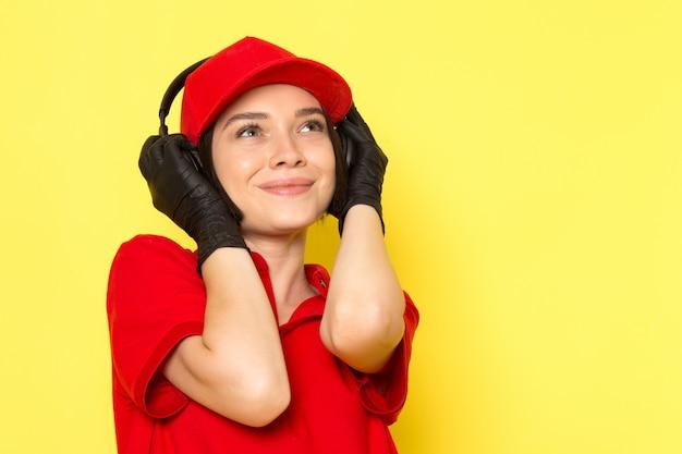 Una vista frontale giovane corriere femminile in uniforme rossa guanti neri e berretto rosso ascoltando musica con espressione felice