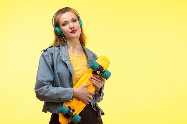Una vista frontale giovane donna moderna in camicia gialla pantaloni neri e cappotto jean tenendo skateboard con auricolari colorati sorridendo