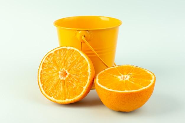 Una vista frontale ha affettato il dolce succoso maturo fresco arancio isolato insieme al piccolo pezzo arancio del canestro sul bianco