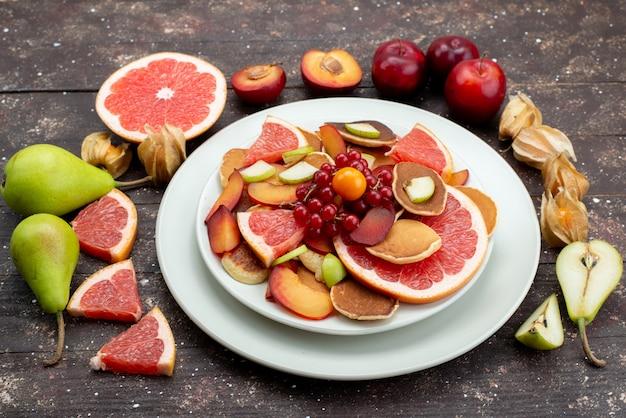 Una vista frontale ha affettato la frutta fresca colorata e succosa all'interno del piatto bianco sugli agrumi in legno dell'alimento di colore della frutta dello scrittorio