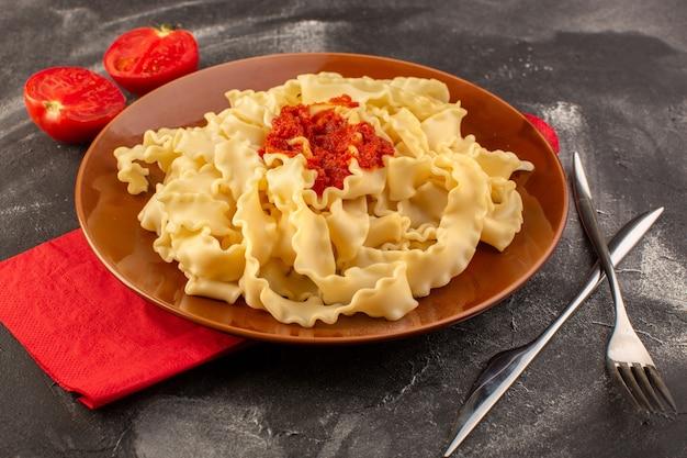 Una vista frontale ha cucinato la pasta italiana con la coltelleria della salsa di pomodoro ed i pomodori all'interno del piatto sulla superficie grigia