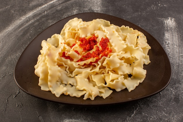 Una vista frontale ha cucinato la pasta italiana con salsa di pomodoro all'interno del piatto sulla superficie grigia